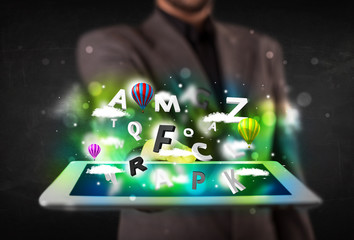 Young person showing tablet with abstract letters and sky
