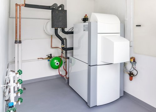 A boiler room with a heating oil warm water system and pipes