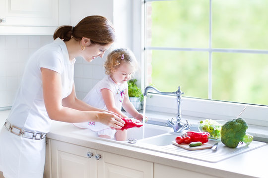 Young beautiful mother and her toddler daughter in kitchen