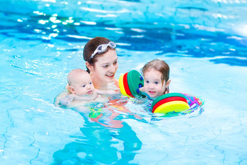 Young active mother swimming with toddler daughter and baby son