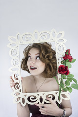 Beautiful young woman posing with white picture frame and roses.