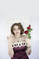 Beautiful young woman posing with picture frame and roses.