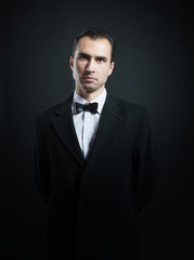 Portrait of a man in tuxedo looking at camera, dark background