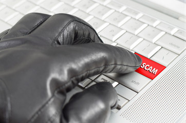Online scamming concept with hand wearing black glove