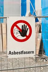 Warnschild - Asbestfasern - an einem Bauzaun