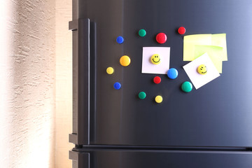 Empty paper sheets and colorful magnets on fridge door