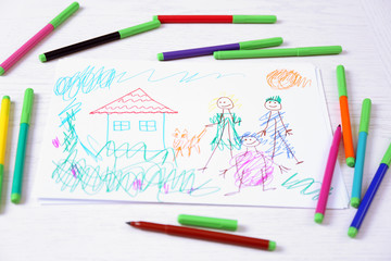 Kids drawing of family and colored pencils on wooden table