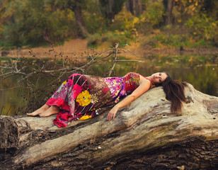 Beautiful girl lying on the tree trunk