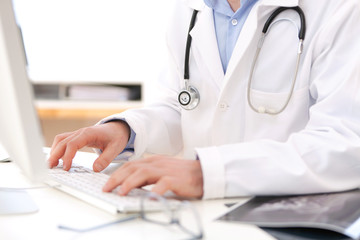 Details of doctor hands typing on keyboard