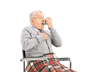 Senior man breathing through his inhaler