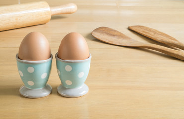 Two eggs in blue polka dot egg cups and baking utensils
