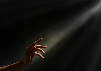 woman's hand reaches for the light rays Wall mural