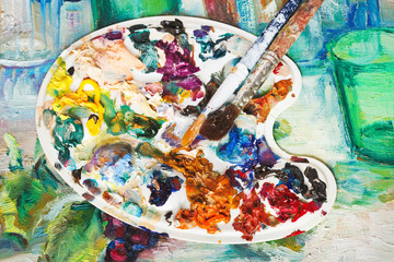 pallette and paintbrushes on picture canvas