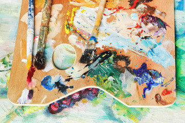 wood used artistic pallette with paintbrushes