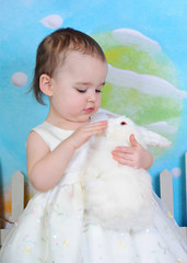 toddler girl petting bunny at easter