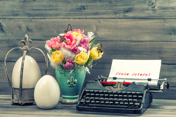 Easter decoration with tulips, eggs and typewriter