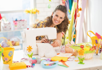 Happy young woman making easter pot holder mitts in studio