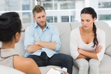 Unhappy couple with arms crossed at therapy session