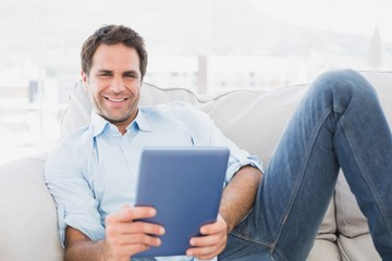 Happy man relaxing on the couch using his tablet