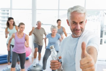 Senior man gesturing thumbs up with people exercising in fitness