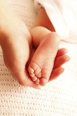 leg cute newborn little baby in mother's hands