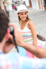 Man taking picture of girlfriend sitting on moto