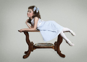 The little girl with bow on her head lying on the table