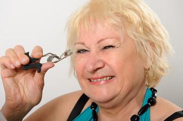 Woman using eyelash curler.