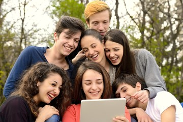Group of young adults browsing a tablet outside