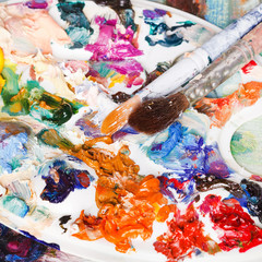 palette with strokes of oils and two paintbrushes