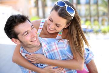 Man giving piggyback ride to girlfriend
