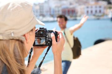 Woman taking picture of boyfriend on tourist journey