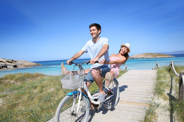 Man giving bike ride to girlfriend on beautiful Island