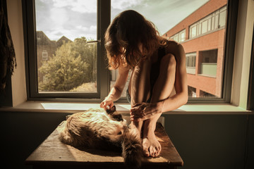 Woman and cat by the window