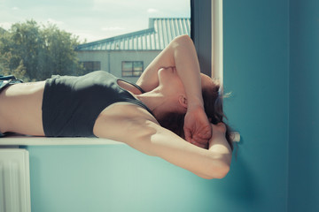 Young woman lying in window