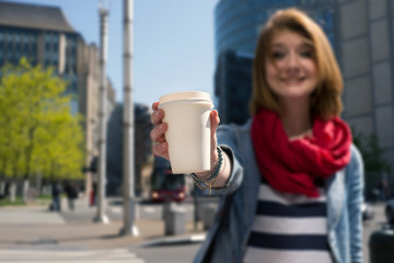 Young woman holding a paper cup and smiling
