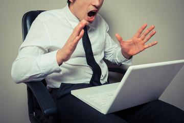 Nervous businessman wih laptop