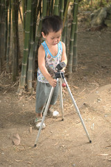 Toddler setting up a camera tripod in the garden