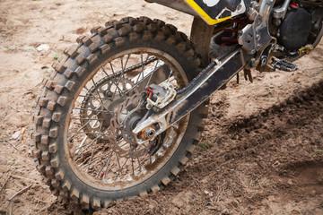 Rear wheel of sport bike. Dirty road, motocross theme