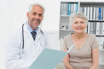 Portrait of a doctor and senior patient with reports