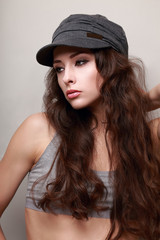 Sexy young woman with long hair in trendy cap. Hipster