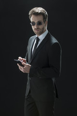 handsome man in black suit using a phone  on a black background