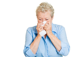 Senior elderly woman with allergy and colds blowing nose