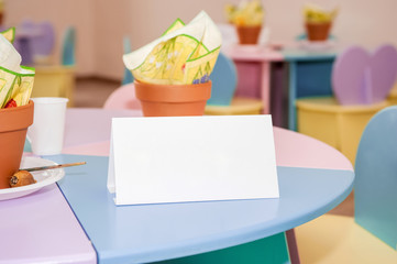 White invitation note on colored table