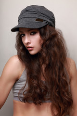 Beautiful long hair trendy woman in cap. Hip-hop style