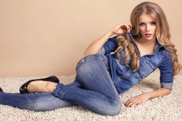 sexy girl with blond hair in jeans clothes lying on carpet