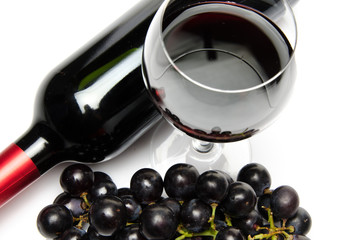 Bottle and glass of wine with black grapes