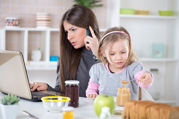 Overworked Businesswoman and her daughter in the morning.
