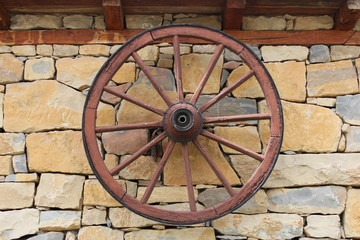 Old decorative wheel on stone wall