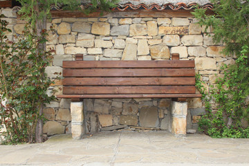 Wooden bench in front of stone fence